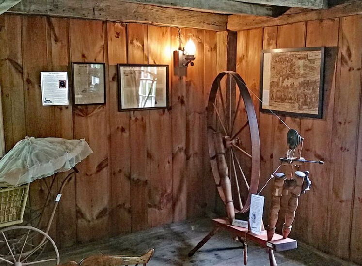 "DINING ROOM: Most families owned both a ""Great Spinning Wheel"" for wool and a pedal-driven foot Trundle wheel for flax and worsted wool with longer strands. The Great Wheel is shown here."