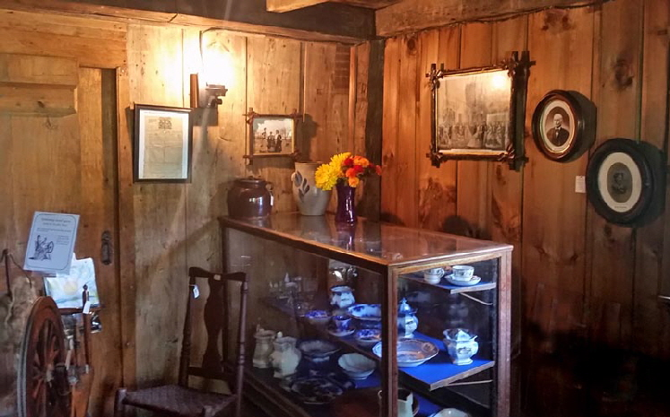 DINING ROOM: Display of various colonial dinnerware. Pictures of the Fisher and Richardson families are on the walls.